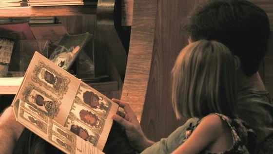 Bambina che legge libro con papà